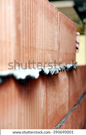 Background of brick wall texture. A classic orange brick wall just installed and still wet concrete. Inside of a building site at the end of a masonry work. - stock photo