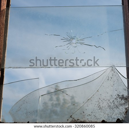 background of broken debris glass in window wooden frame backdrop against blue sky with clouds - stock photo