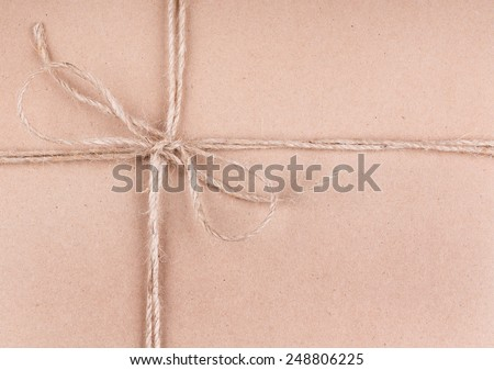 Background of brown wrapping paper tied with string - stock photo