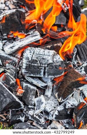 Background of burning coals laying on the ground - stock photo