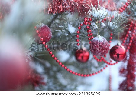Background of Christmas or New year holiday snowy green pine tree with decoration frost toys under snow Red balls on a snow covered branch  Outdoor or outside cold backdrop Selective focus  - stock photo