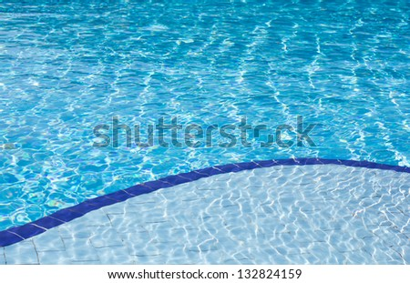 Background of clear blue water with sun reflections in an outdoor swimming pool with two different depths, a shallow and a deep depth. - stock photo