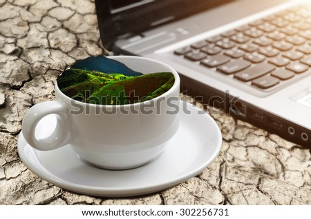 background of coffee cup shape with green field inside on the crack earth. - stock photo