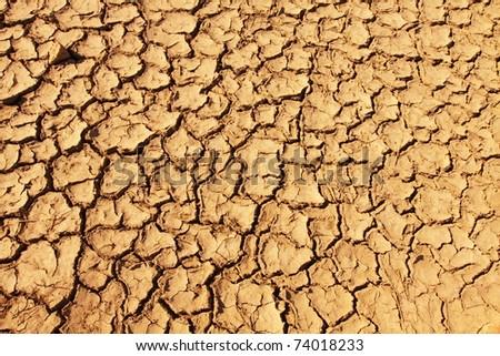 Background of cracked soil on desert - stock photo