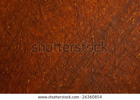 Background of crushed deep reddish brown, creased rice paper with tiny flecks of gold - stock photo