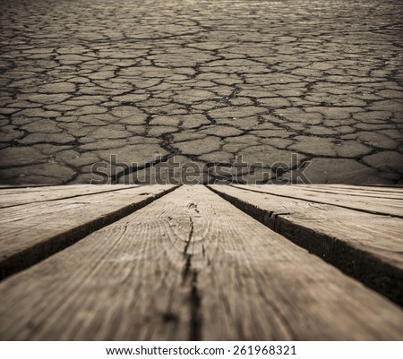 background of dark brown cracked ground soil in desert and old retro vintage aged wooden texture plank on floor backdrop Empty space for inscription or object Idea of disaster in nature and ecology - stock photo