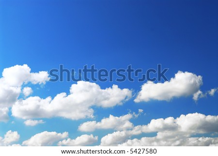 Background of deep blue sky with white fluffy clouds at the bottom - stock photo