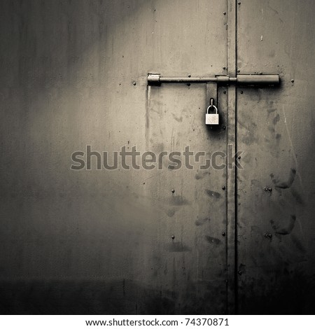 Background of door with lock in metal material and copyspace on wall. - stock photo