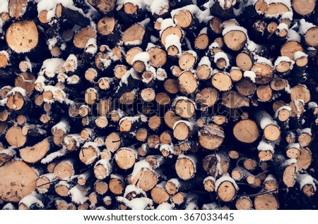Background of dry chopped firewood logs stacked up on top of each other in a pile. Stack of wood cut with snow for fireplace prepared for winter. Chopped logs for winter fire. Firewood pattern. - stock photo