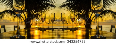 Background of eight 8 glasses champagne vine staying on wood table chairs against palm silhouette sunset yellow sky with clouds couple in water on coast and sun light reflection on boards After dinner - stock photo