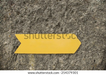 Background of empty Blank metal yellow arrow on grunge stone gray wall texture backdrop Metallic gold sign show the direction pointer - stock photo