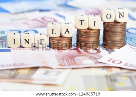 """Background of Euro banknotes on the ground, heaps of cent coins on top building a growth chart. Letter dices forming the word """"Inflation"""". Short Depth of field with front and back blurred. - stock photo"""