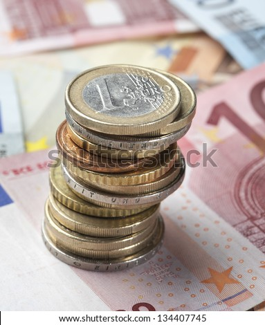 Background of Euro banknotes with coins standing on top. Short Depth of field with front and back part blurred out of focus.