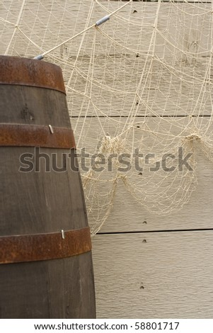 Background of fish net, weathered boards and a barrel. - stock photo