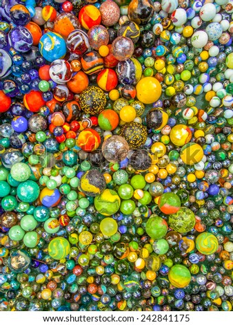 Background of glass marbles of different sizes in a color pattern - stock photo
