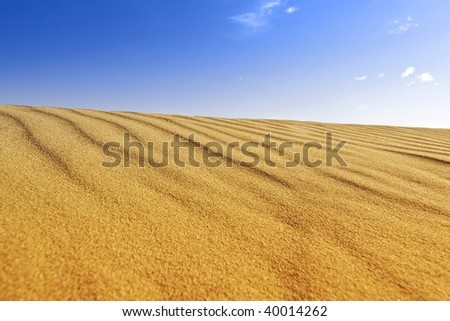 Background of golden sand dune and blue sky