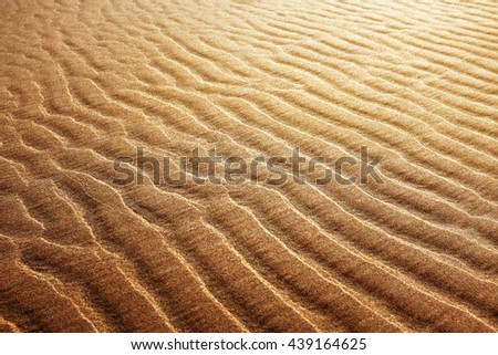 Background of golden sand with rippled pattern at low tide - stock photo