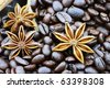 Background of gourmet coffee ingredients with star anise and whole coffee beans. Selective focus on lower portion of image with shallow depth of field. - stock photo