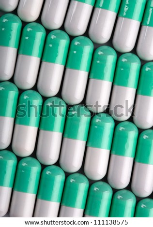 Background of green-white pills in a rows - stock photo