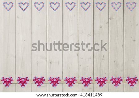 background of light wooden planks, and flower heart border with paeony and corn flowers - stock photo