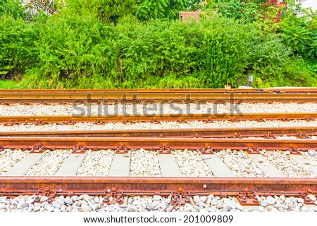 Background of many parallel railroad tracks and bushes - stock photo
