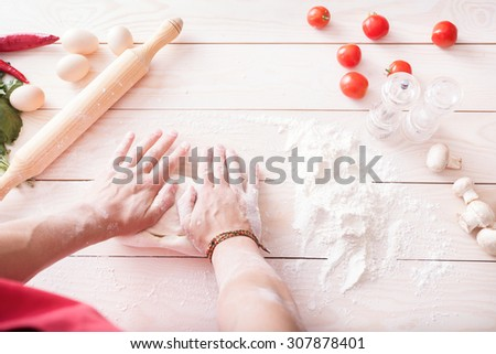 background of men's hands knead the dough. Ingredients for cooking flour products or dough (bread, muffins, pie, pizza dough) - stock photo