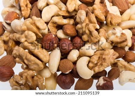 background of mixed nuts -  hazelnuts, walnuts, cashews,  pine nuts - stock photo
