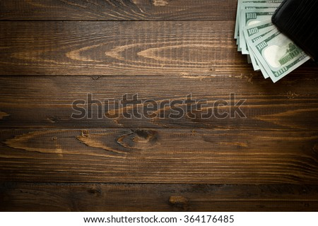 Background of money in leather purse on wood with copyspace - stock photo