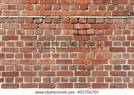 Background of old red brick wall with scratches, holes and gaps - stock photo