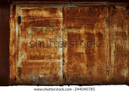 Background of old rusty steel garage door and hinge. - stock photo