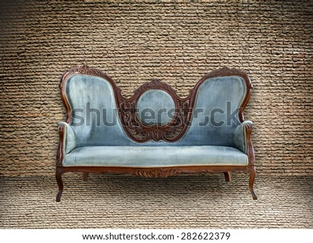 Background of old vintage brick wall and old vintage sofa - stock photo