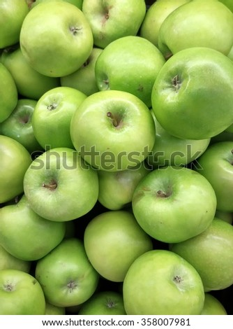 background of organic imported fresh ripe green apples on display at local farmer's market departmental store - stock photo