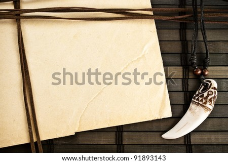 Background of paper sheet, decorative trophy tooth and leather straps on a wooden background.