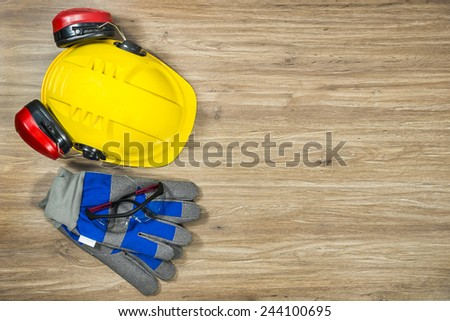 Background of personal safety accessories on a wooden surface. Items include a hard hat with ear protection attached, safety goggles and working gloves - stock photo