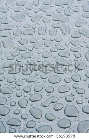 Background of raindrops on a garden table.