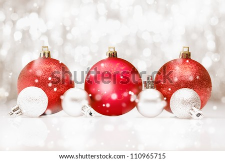 Background of red Christmas baubles in falling snow with bokeh and copyspace for your seasonal greetings - stock photo