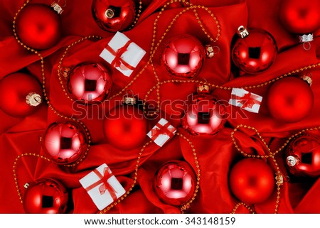 Background of red Christmas tree balls, little gift boxes and gold decorations on red shiny silk fabric