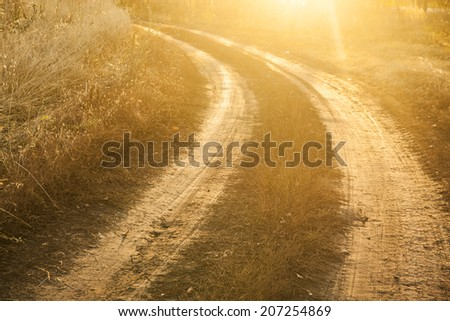 Background of red sunset over rural textured land road near yellow reap summer or autumn wheat field - stock photo