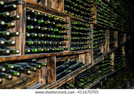 Background of retro vintage dusty Wine bottles in perspective Wooden shelf from floor to ceiling Light from open door on warehouse cellar. private collection. - stock photo