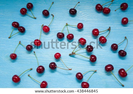 Background of ripe cherries. Fresh cherries scattered on a wooden table. delicious and healthy fruits on blue table. Top view - stock photo