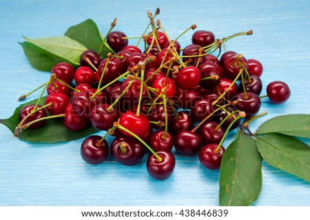 Background of ripe cherries. Pile of fresh and tasty cherries. Fresh cherries scattered on a blue wooden table.  - stock photo