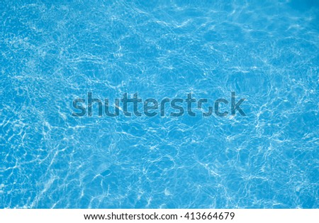 Background of rippled pattern with bright blue swimming pool water - stock photo