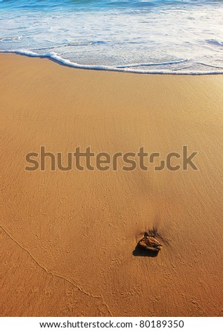 Background of sea sand and surf with a single pebble in foreground - stock photo