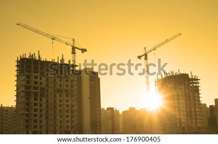 Background of  silhouette building crane lift loads with sun set rays yellow cloudy evening sky backdrop Construction site at orange sunset - stock photo