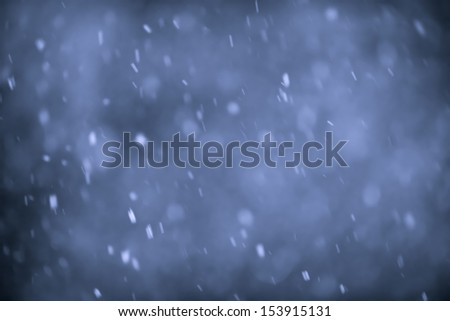 Background of snow flurry falling at night with motion blur - stock photo