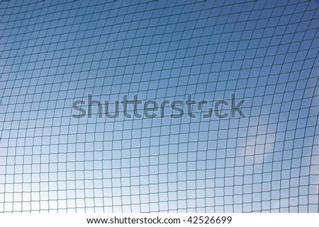 Background of sports net against blue sky
