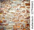 Background of stone wall texture. closeup of ancient cracked stone wall - stock photo