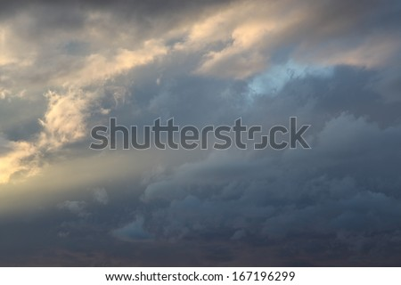 Background  of sunlight on wispy clouds, with sun ray into soft gray clouds/Sunlight and Sun Ray touch Cloudy Heavens Background of Soft Blue and Gray/Sunshine lights up gray cloudy background  - stock photo