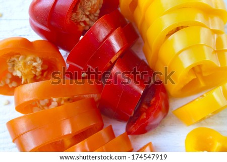 Background of sweet  peppers sliced in pieces on white wooden background