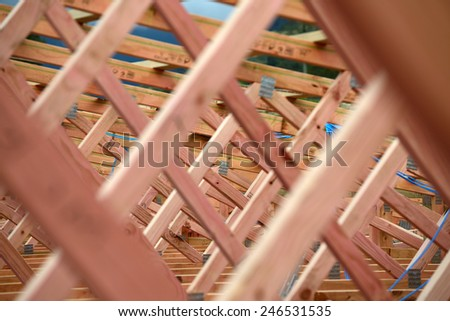 background of treated timber framing in the roof of a new building - stock photo